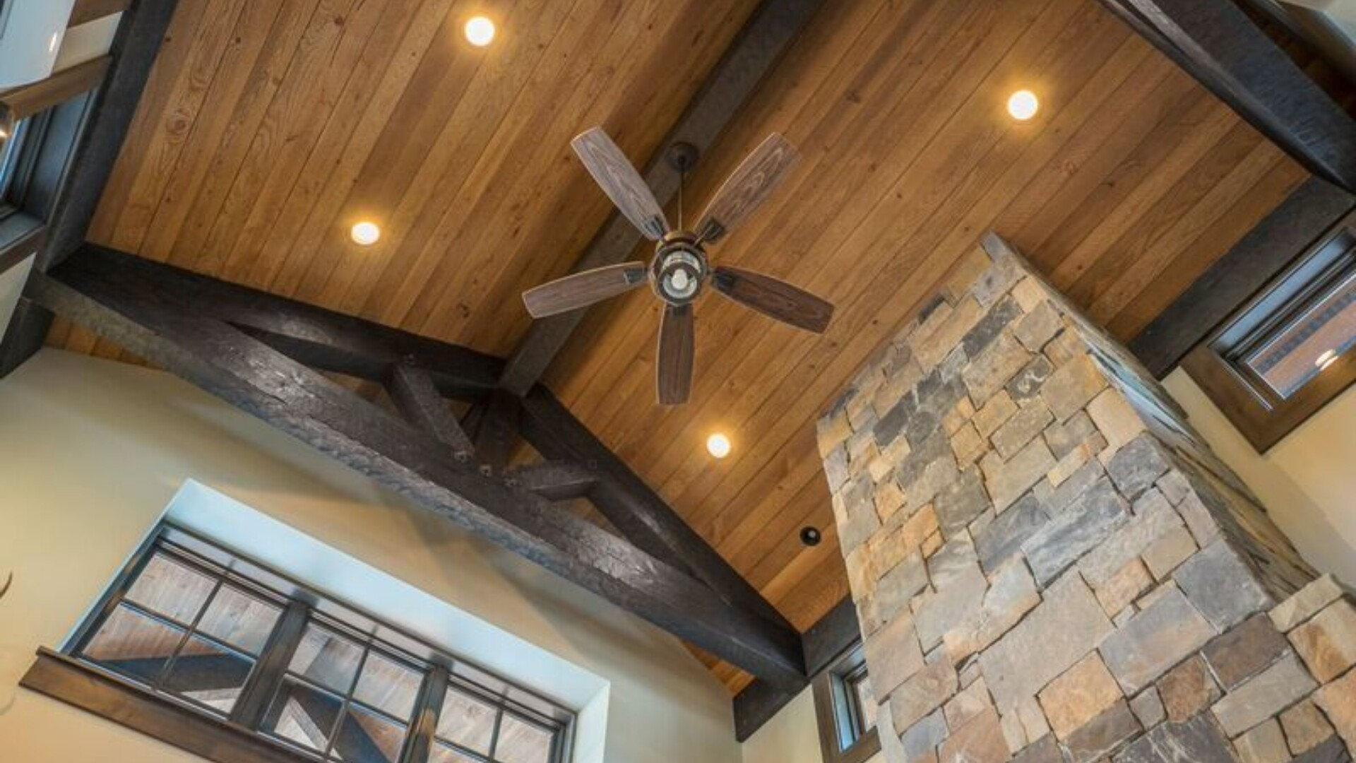wooden ceiling with heavy wooden trusses and a ceiling fan