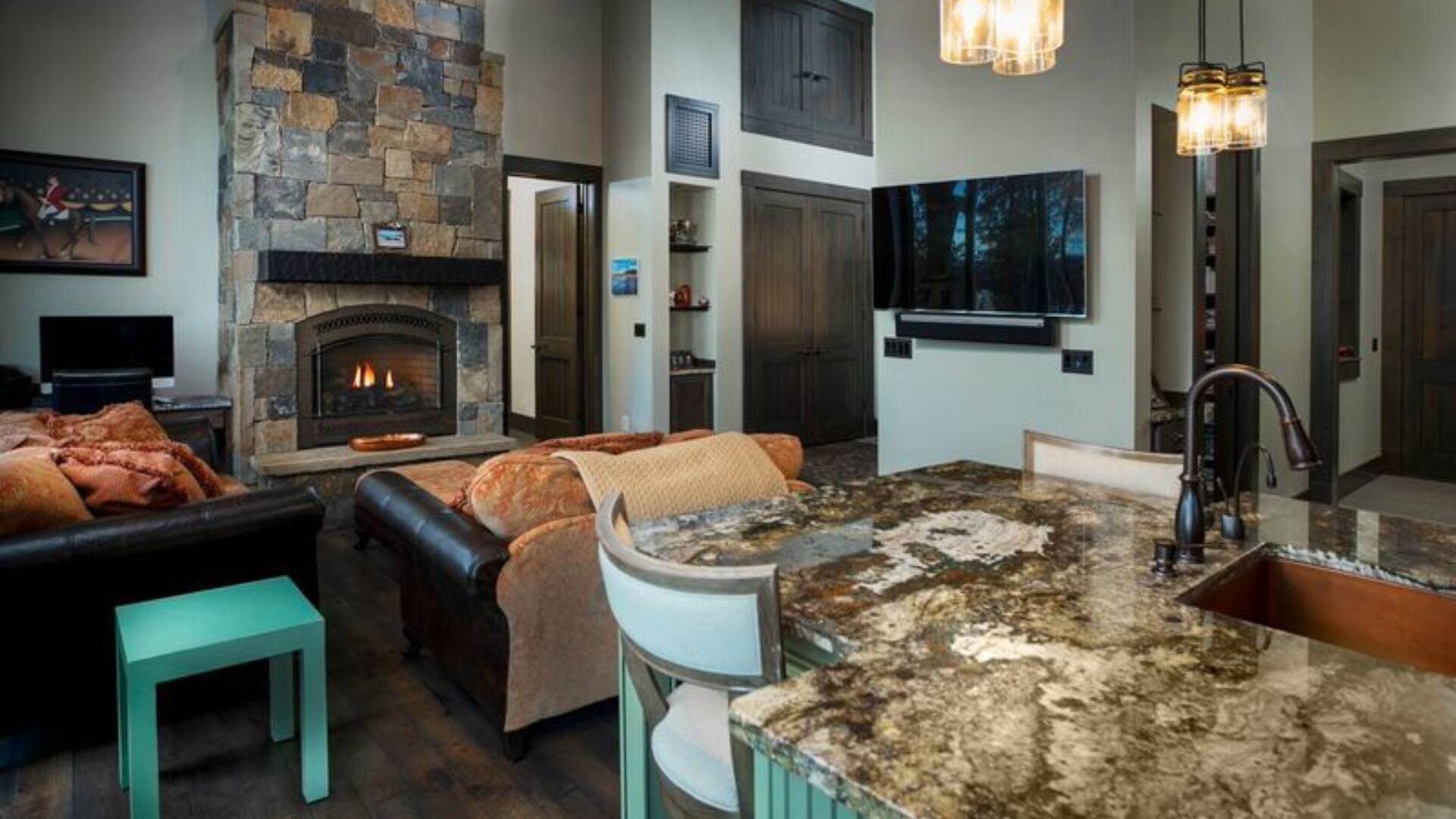 looking out from the pask guest house kitchen into a small living area with couches and a large stone fireplace
