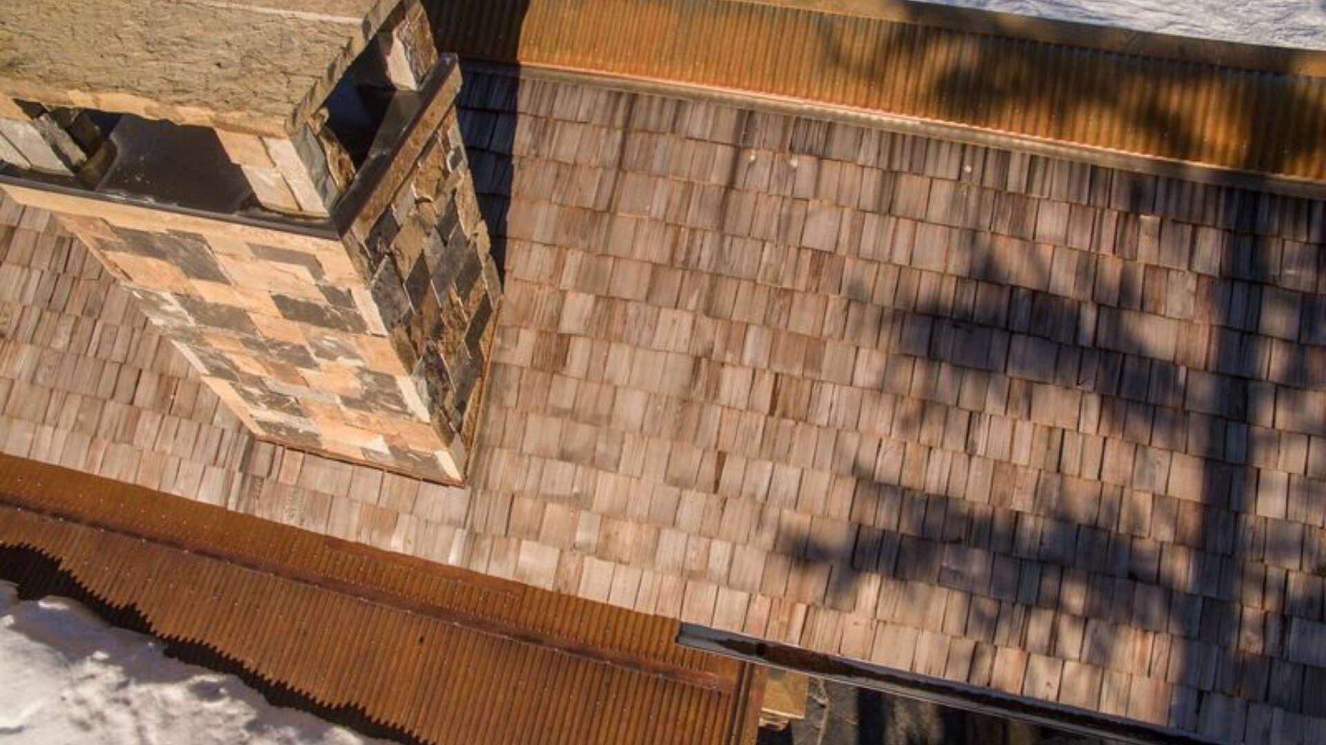 aerial view of pask guest house roof with wooden shingles and a large stone chimney