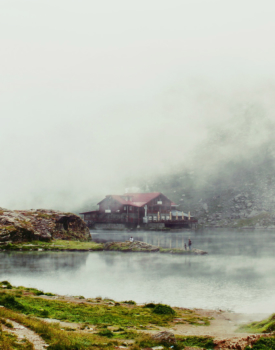 waterfront home on a river with mist coming over background mountains